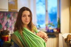 Mujer joven con el bebé del niño recién nacido en una honda con un fondo borroso en casa imágenes de archivo libres de regalías