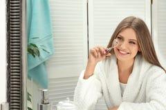 Mujer joven con el bigudí de la pestaña cerca del espejo fotos de archivo