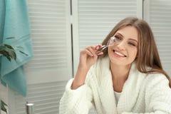 Mujer joven con el bigudí de la pestaña cerca del espejo fotos de archivo libres de regalías