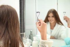 Mujer joven con el bigudí de la pestaña cerca del espejo en cuarto de baño fotos de archivo