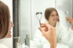 Mujer joven con el bigudí de la pestaña cerca del espejo en cuarto de baño imágenes de archivo libres de regalías