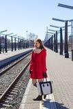 Mujer joven con el bolso en una estación de tren Imagenes de archivo