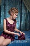 Mujer joven con el bolso que se sienta en cama Foto de archivo libre de regalías