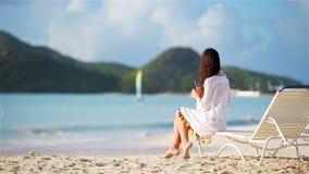 Mujer joven con el cóctel sabroso en la playa blanca almacen de metraje de vídeo