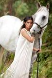 Mujer joven con el caballo blanco