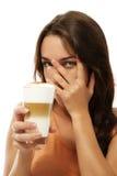 Mujer joven con el café del macchiato del latte que la oculta Fotos de archivo libres de regalías