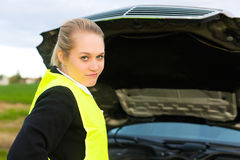 Mujer joven con el capo motor abierto del coche en la calle fotografía de archivo