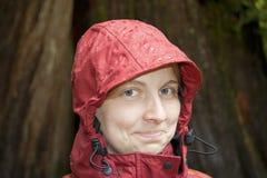 Mujer joven con el capo motor en la lluvia Imagenes de archivo