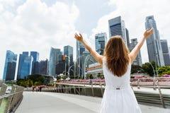 Mujer joven con el centro de la ciudad aumentado de los brazos adentro de Singapur Fotografía de archivo libre de regalías