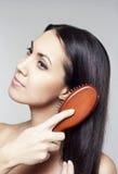 Mujer joven con el cepillo para el pelo Fotos de archivo