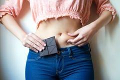 Mujer joven con el chocolate que muestra su grasa Imagenes de archivo