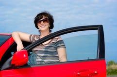 Mujer joven con el coche rojo Imágenes de archivo libres de regalías