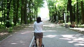 Mujer joven con el cochecito que camina en el bosque almacen de metraje de vídeo