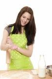 Mujer joven con el contacto de balanceo que agrega la harina a la pasta Fotos de archivo libres de regalías
