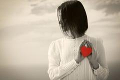 Mujer joven con el corazón de la tarjeta del día de San Valentín Fotos de archivo