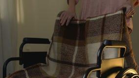 Mujer joven con el corazón pesado que quita a sus madres silla de ruedas, pérdida de familia almacen de metraje de vídeo