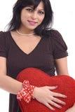 Mujer joven con el corazón rojo grande de la felpa Fotos de archivo