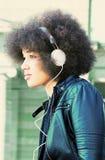 Mujer joven con el corte y los auriculares afro del pelo Fotografía de archivo