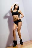 Mujer joven con el cuerpo perfecto en ropa de deportes negra Foto de archivo