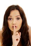 Mujer joven con el dedo en los labios Fotos de archivo libres de regalías