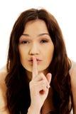 Mujer joven con el dedo en los labios Fotografía de archivo libre de regalías