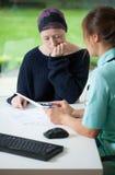 Mujer joven con el doctor que visita del cáncer Imágenes de archivo libres de regalías