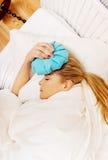 Mujer joven con el dolor de cabeza, sosteniendo un hielo-bolso al lado de su frente Fotos de archivo libres de regalías