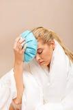 Mujer joven con el dolor de cabeza, sosteniendo un hielo-bolso al lado de su frente Imágenes de archivo libres de regalías