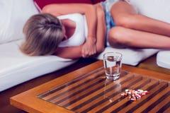 Mujer joven con el dolor de estómago que miente en el sofá Medicina y él fotos de archivo libres de regalías