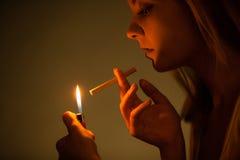 Mujer joven con el encendedor que enciende para arriba el cigarrillo El fumar de la muchacha Foto de archivo libre de regalías