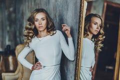 Mujer joven con el espejo imagenes de archivo