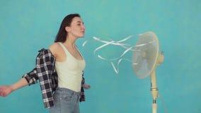 Mujer joven con el fan eléctrico que goza del aire fresco MES lento almacen de metraje de vídeo