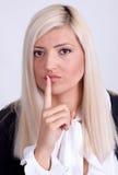 Mujer joven con el finger en los labios sobre el fondo blanco Imagenes de archivo