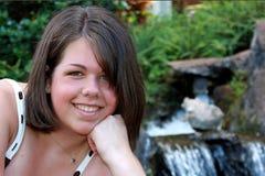Mujer joven con el fondo de la cascada Imagen de archivo libre de regalías
