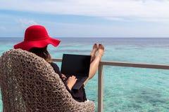 Mujer joven con el funcionamiento rojo del sombrero en un ordenador en un destino tropical imagen de archivo libre de regalías