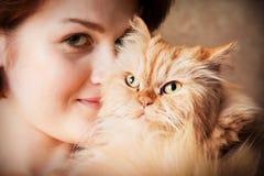 Mujer joven con el gato persa Imagenes de archivo