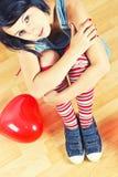Mujer joven con el globo rojo del corazón Foto de archivo libre de regalías