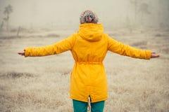 Mujer joven con el goce aumentado de las manos al aire libre Foto de archivo