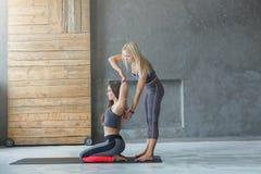 Mujer joven con el instructor de la yoga en el club de fitness, gomukhasana fotos de archivo