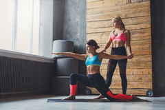 Mujer joven con el instructor de la yoga en el club de fitness, actitud del guerrero Imágenes de archivo libres de regalías
