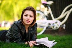 Mujer joven con el libro de lectura de la bicicleta en parque de la ciudad en la hierba Fotos de archivo