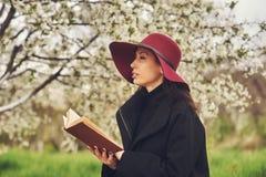 Mujer joven con el libro en un jardín floreciente Imagen de archivo libre de regalías