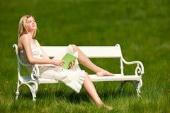 Mujer joven con el Libro verde que se sienta en el banco blanco Imagenes de archivo