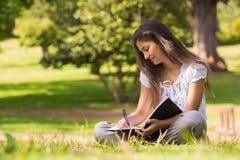 Mujer joven con el libro y pluma en parque Fotos de archivo