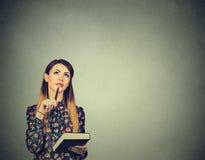 Mujer joven con el libro y pluma que piensan soñando la mirada para arriba Imágenes de archivo libres de regalías