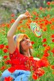 Mujer joven con el lollipop colorido en campo Imagenes de archivo