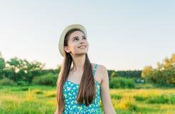 Mujer joven con el manojo de manzanillas en un campo con la hierba alta Fotografía de archivo libre de regalías