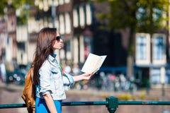 Mujer joven con el mapa de la ciudad en ciudad europea en Amsterdam Imagenes de archivo