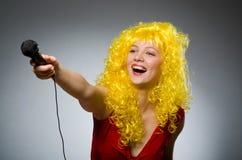 Mujer joven con el mic imagen de archivo