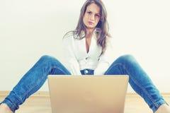 Mujer joven con el ordenador portátil Imagenes de archivo